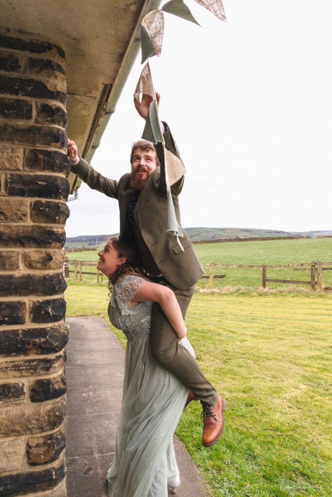 bridesmaid lifts groomsman hanging bunting west yorkshire wedding  rishworth oxford wedding photographer