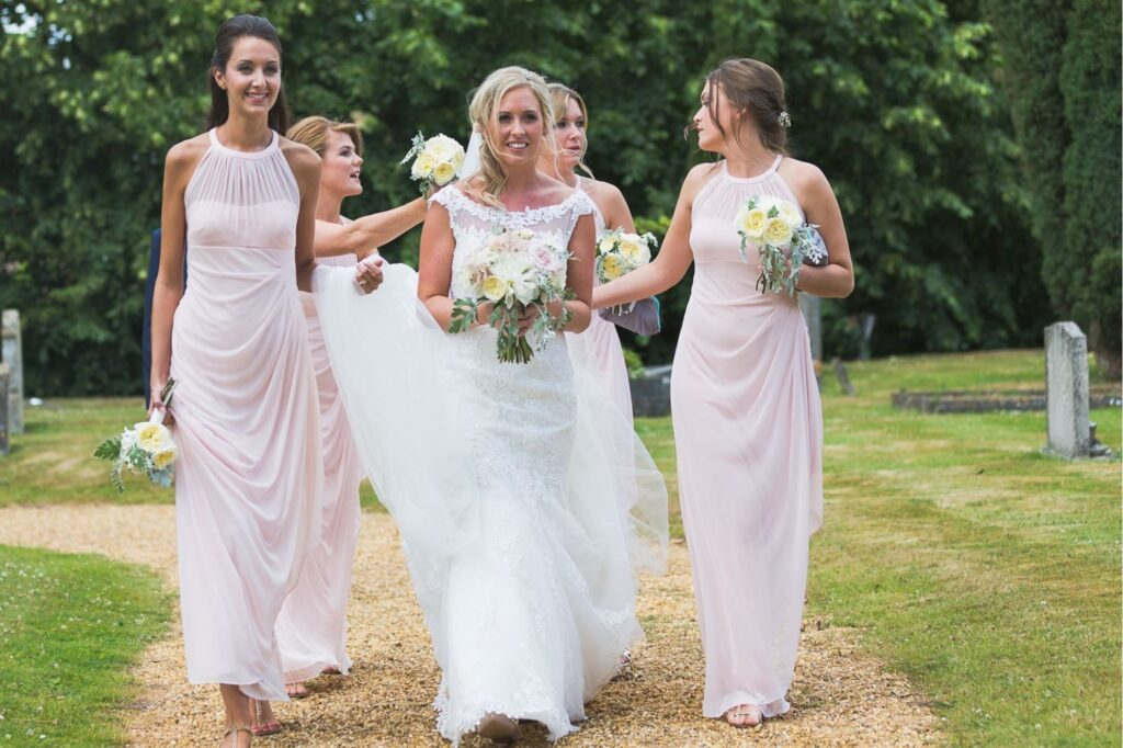 01 bride bridesmaid walk through churchyard to church marrage ceremony oxfordshire wedding photographer