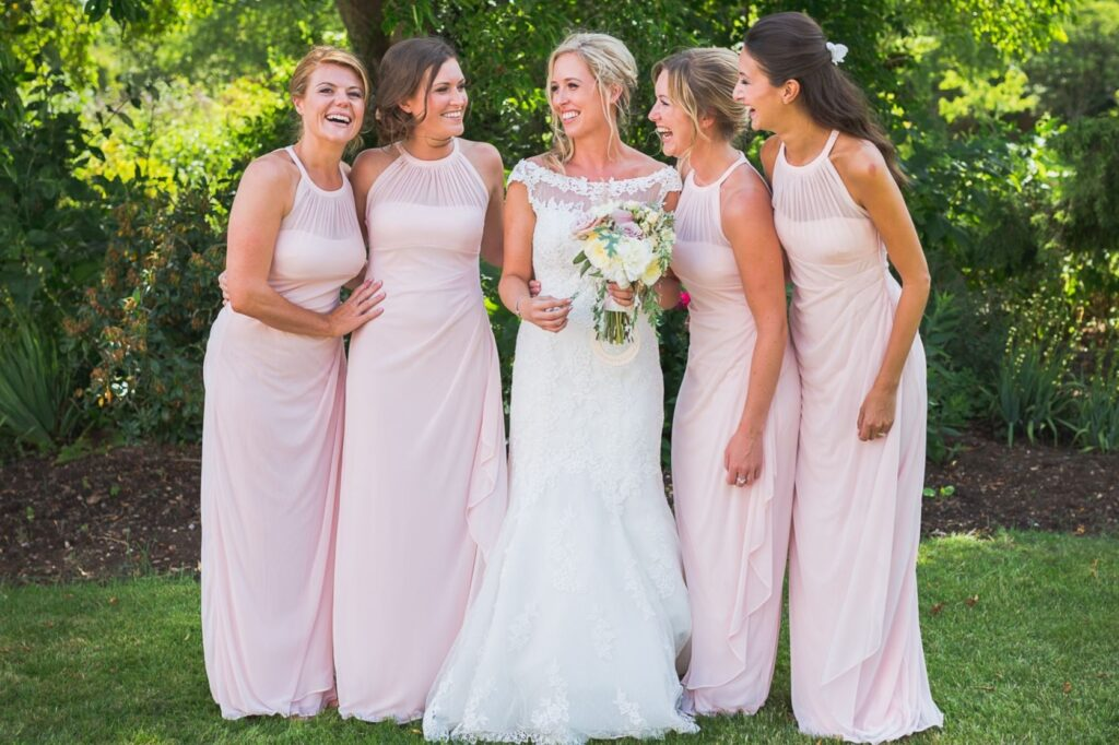 06 laughing bride white dress flowers bouquet with bridesmaids in pink dresses before church marriage ceremony oxfordshre wedding photography