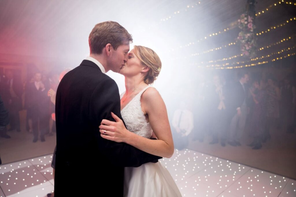 17bride groom kiss under fairy lights marquee reception blenheim palace woodstock oxfordshire oxford wedding photographers