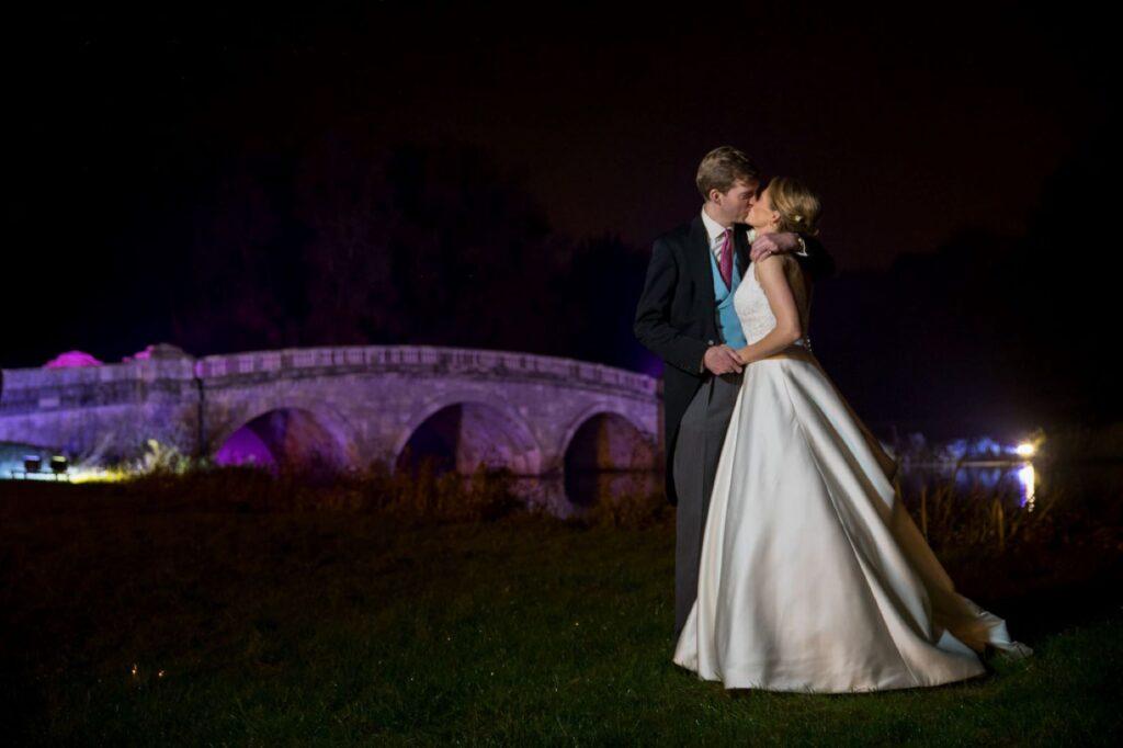 19 bride groom kiss beside floodlit bridge blenheim palace grounds woodstock oxfordshire wedding photography