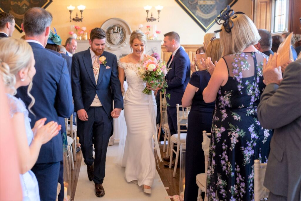 28 guests applaud bride groom walking down aisle the elvetham hartley wintney hampshire oxford wedding photography