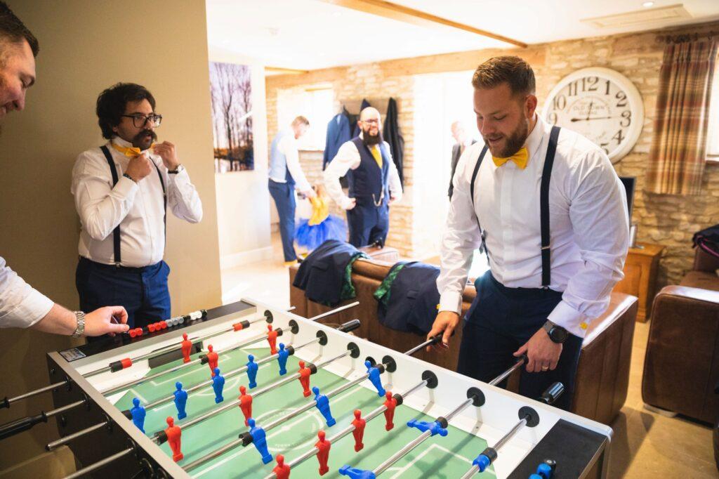 groomsmen play table football oxford wedding photography