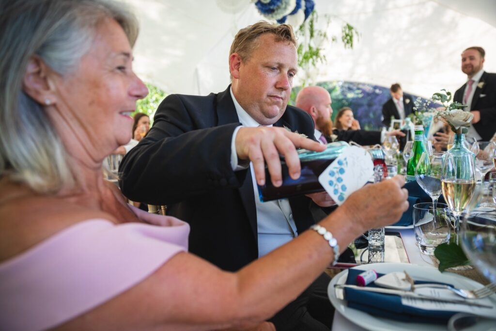 102 groomsman pours drink marquee wedding breakfast winkfield berkshire oxfordshire wedding photography