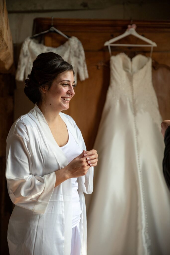 12 smiling bride hanging gown bridal preparation pauntley court gloucester oxfordshire wedding photography
