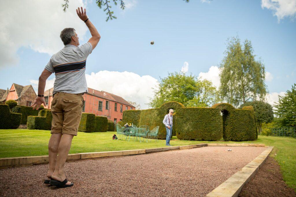 17 groomsmen play petanque pauntley court grounds gloucester oxfordshire wedding photographers