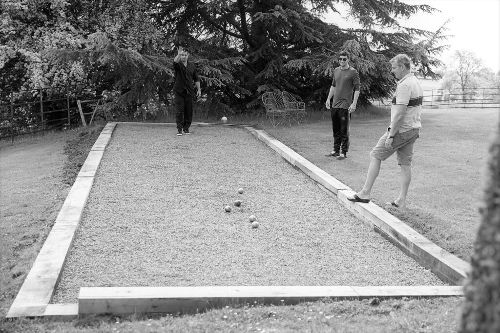 18 groom throws petanque boule pauntley court grounds gloucester oxfordshire wedding photography