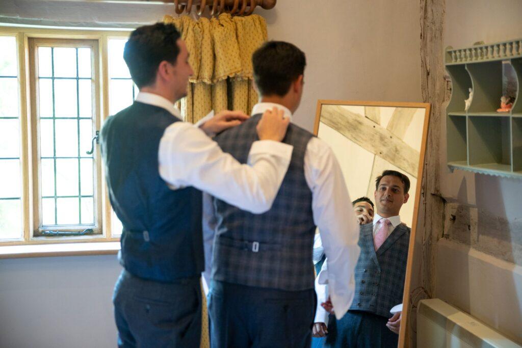 21 groomsman assists groom prep pauntley court gloucester oxford wedding photography
