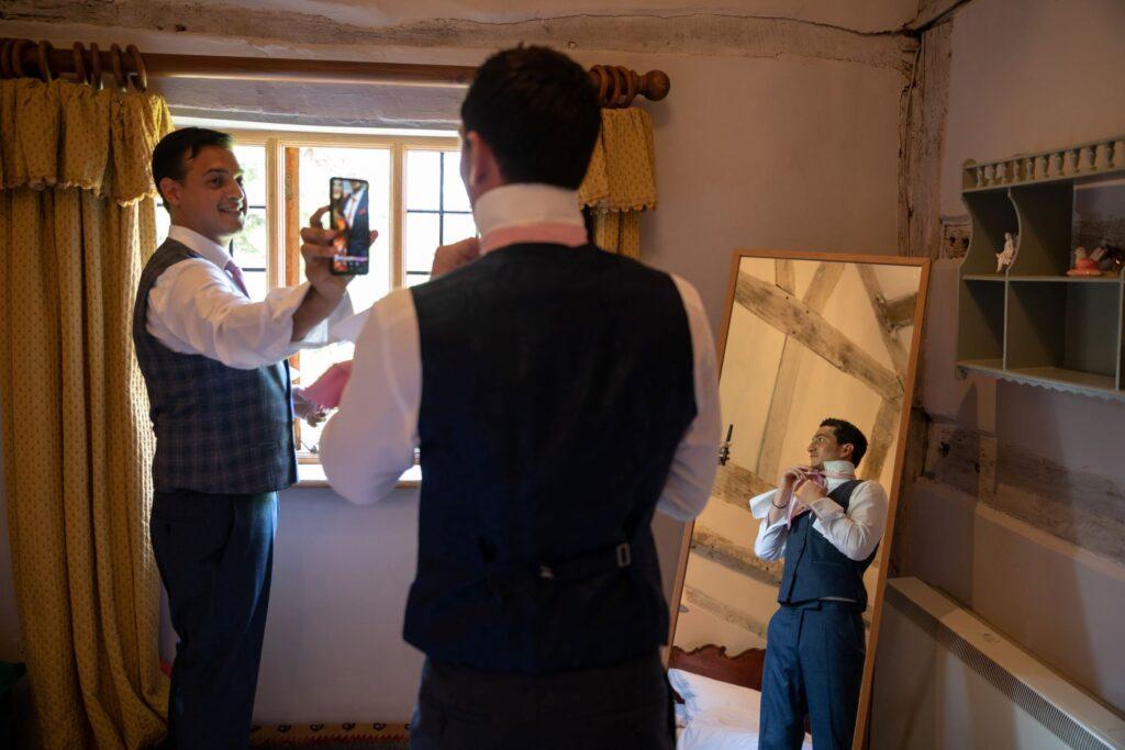 23 groomsman checks tie groom preparation pauntley court gloucester oxfordshire wedding photographers