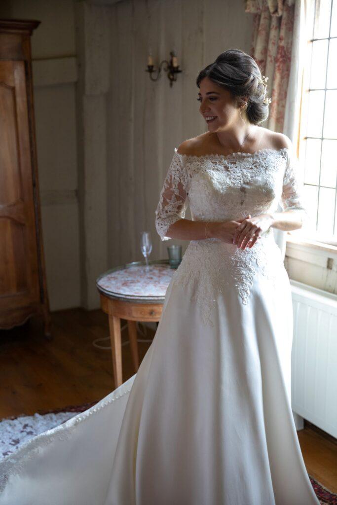 26 smiling bride displays wedding gown bridal prep pauntley court gloucester oxford wedding photographers