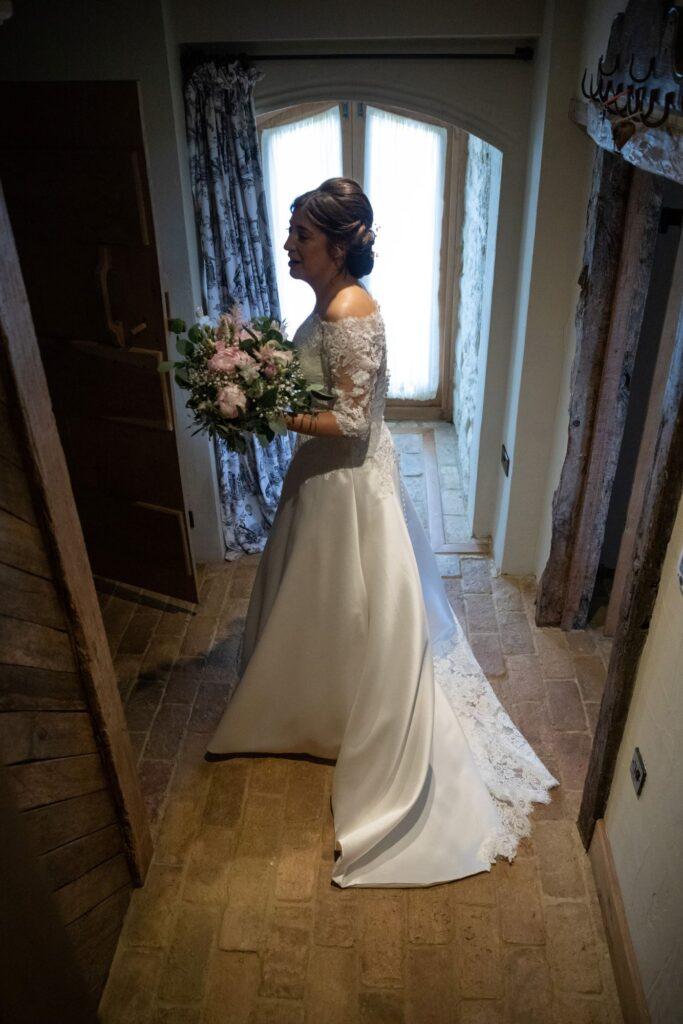 32 bride exits bridal prep room holding bouquet pauntley court gloucestershire oxford wedding photographers