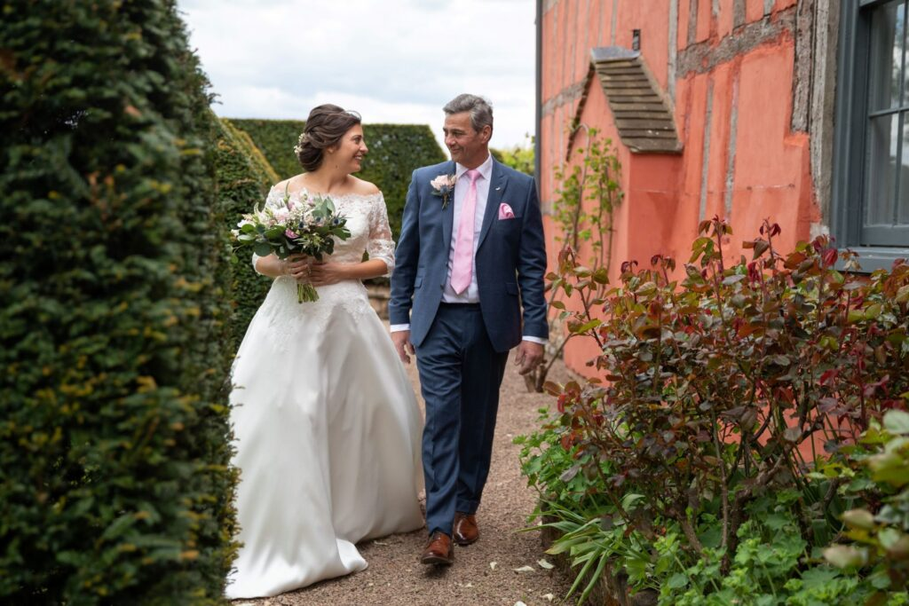 38 smiling bride escorted to marriage ceremony pauntley court gloucester oxford wedding photographers