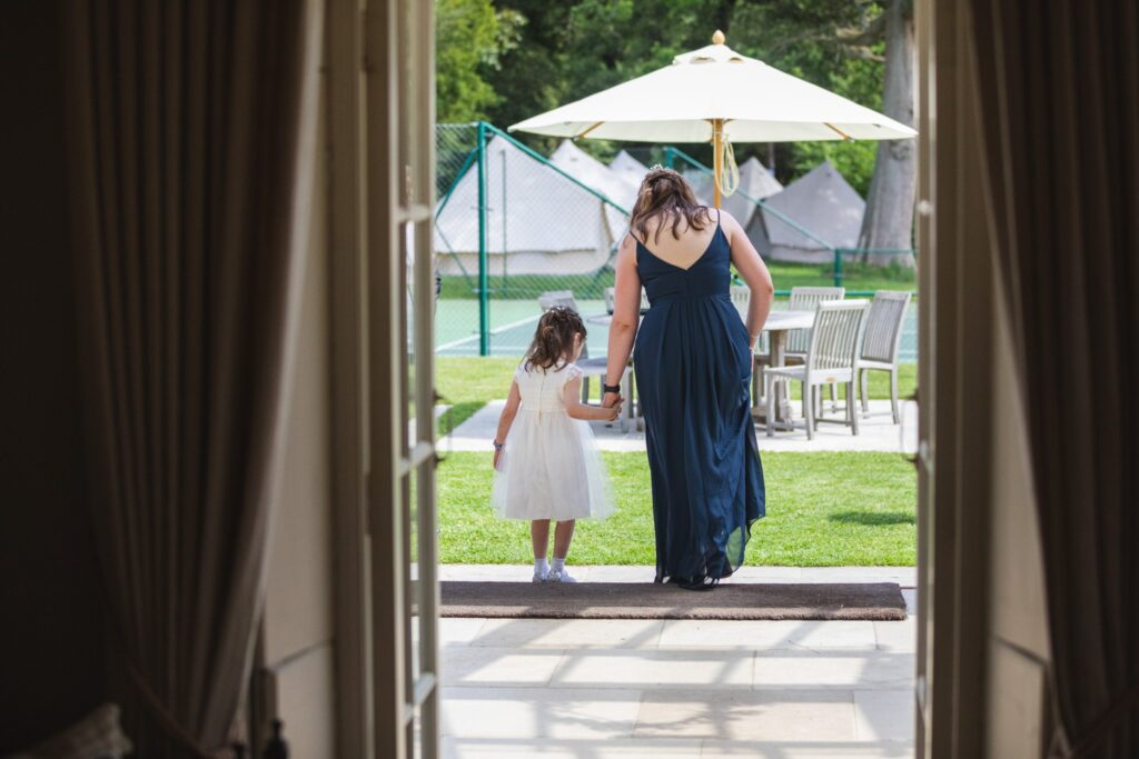 45 bride holds flowergirls hand bridal prep winkfield berkshire oxfordshire wedding photographers