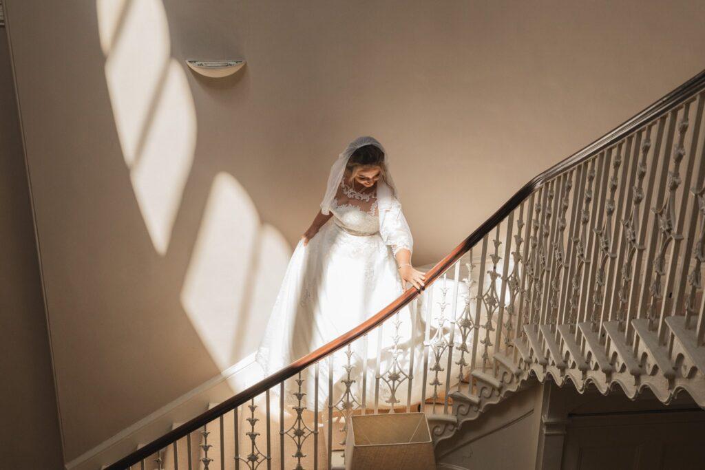 51 bride ascends staircase bridal prep winkfield berkshire oxford wedding photographers