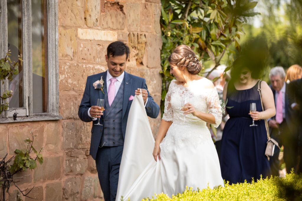 60 groom carries brides dress train pauntley court garden reception gloucester oxfordshire wedding photographers