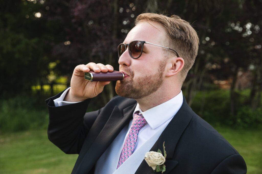 60 groom sips whisky flask winkfield windsor berkshire oxfordshire wedding photographers