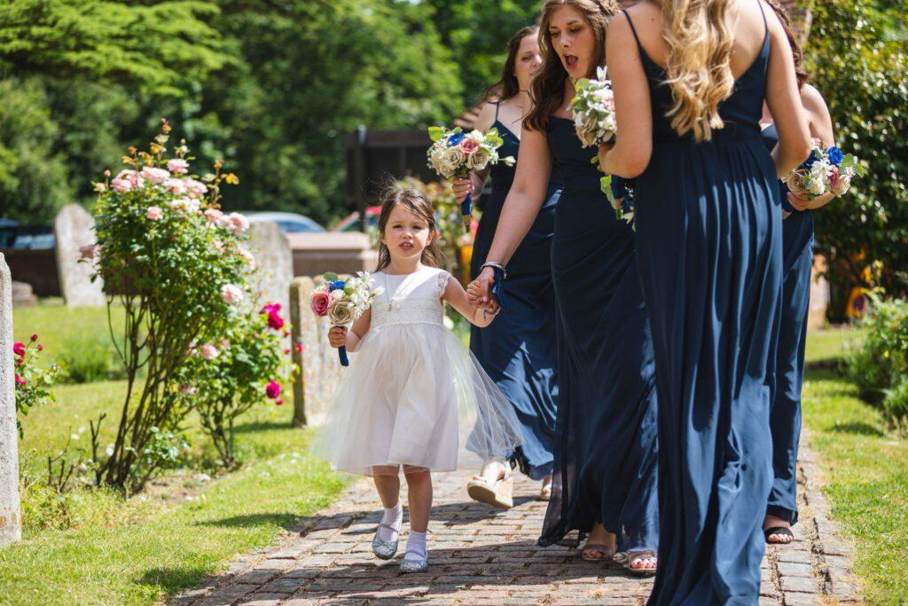 67 bridesmaid holds flowergirls hand st marys churchyard winkfield berkshire oxfordshire wedding photography