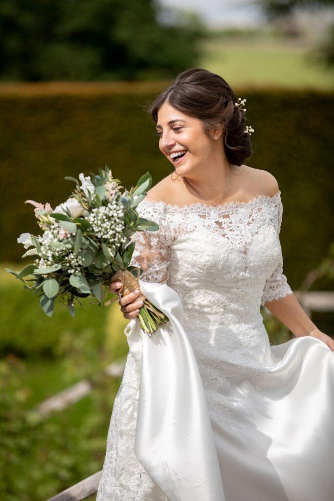 77 laughing bride carries bouquet pauntley court formal garden gloucester oxford wedding photographers