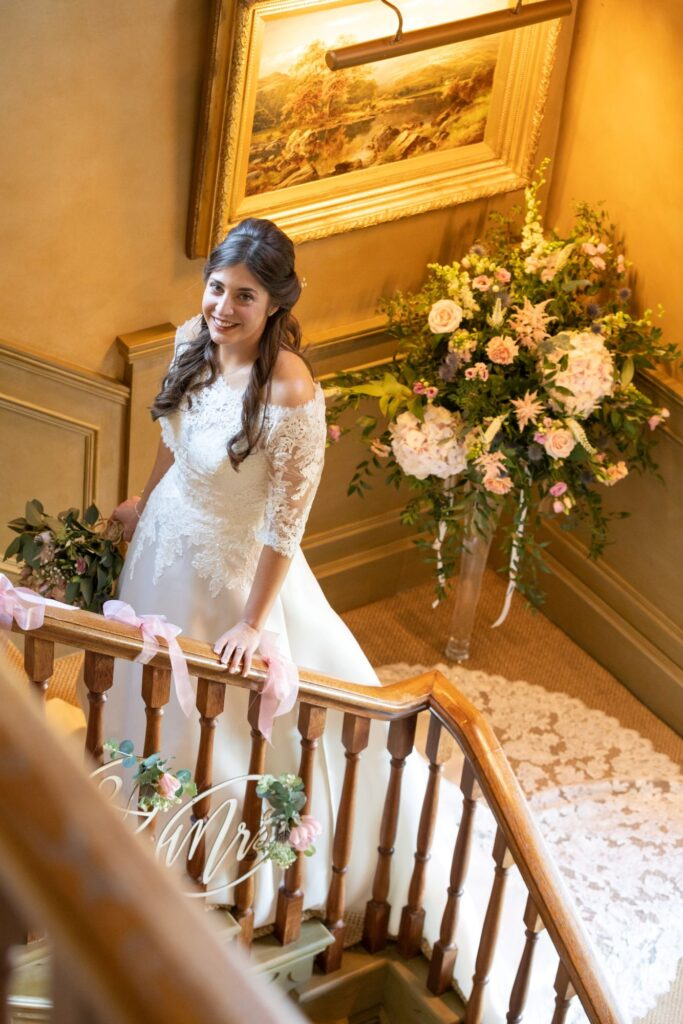 78 bride holds bouqet climbs stairs pauntley court gloucestershire oxfordshire wedding photographer
