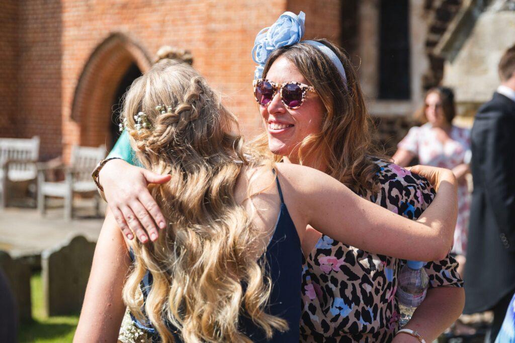 83 guest hugs bridesmaid st marys churchyard winkfield berkshire oxfordshire wedding photography